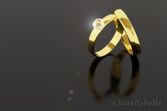 Pair of gold and diamond wedding rings isolated on dark background. 3d illustration.