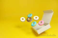 Donuts coming out of a box on a yellow background. 3d illustration.