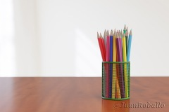 Set of colored pencils in a basket on a wooden table and white background. 3d illustration.